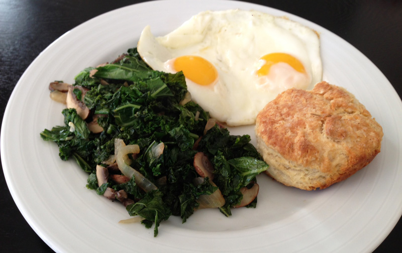 An example of a brunch meal at home: sauteed kale & mushrooms; eggs; biscuit