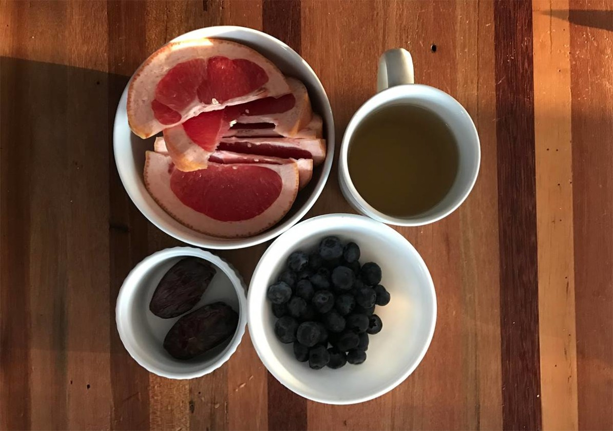 Breakfast featuring grapefruit, blueberries, and dates with green tea.
